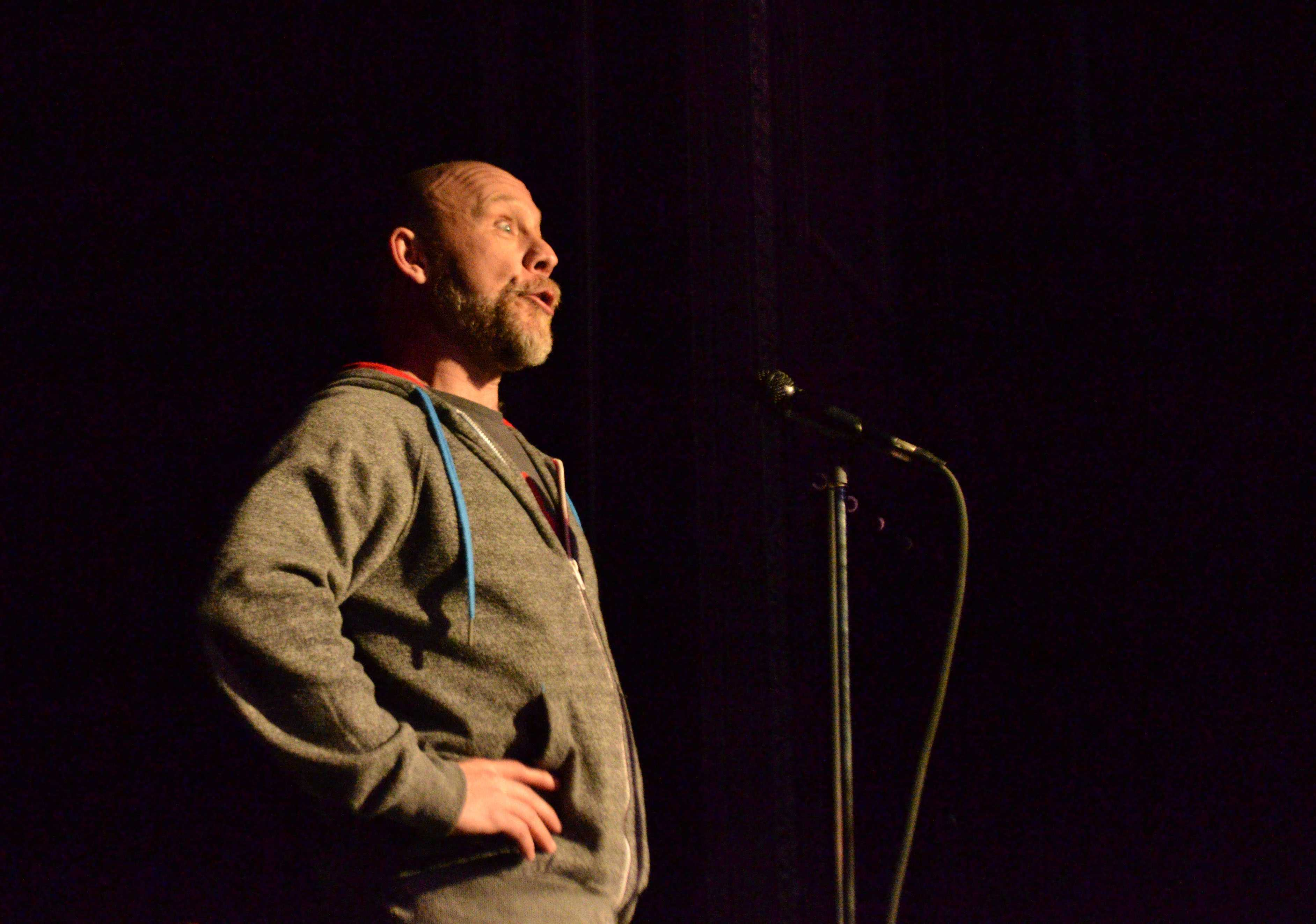 Featured poet, Buddy, interludes the competing poets at the slam
