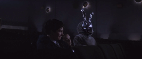 "Jake Gyllenhaal, Jena Malone, and a mysterious figure sit in an empty movie theater in ""Donnie Darko""."