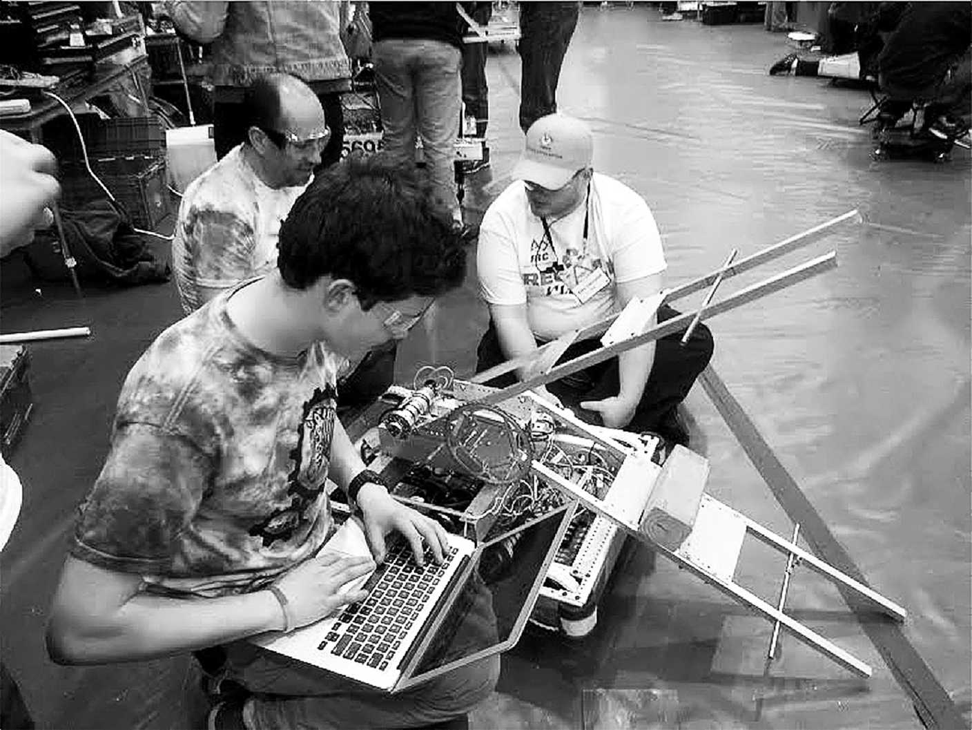 A member of Zebrotics works with team mentors to de-bug the robot's code and ensure that it follows regulation.