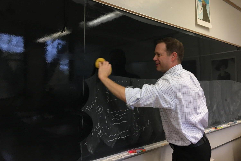 Ken McGraw cleans his blackboard.